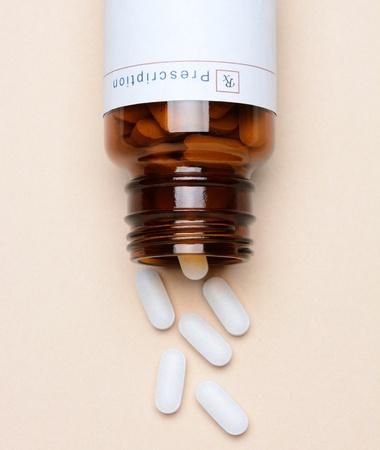 pastillas: Vista superior de una botella de medicina de la prescripci�n de vidrio por su lado con p�ldoras derramando sobre la superficie Foto de archivo