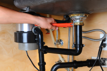 Closeup of a plumber using a wrench to tighten a fitting beneath a kitchen sink  Only the man
