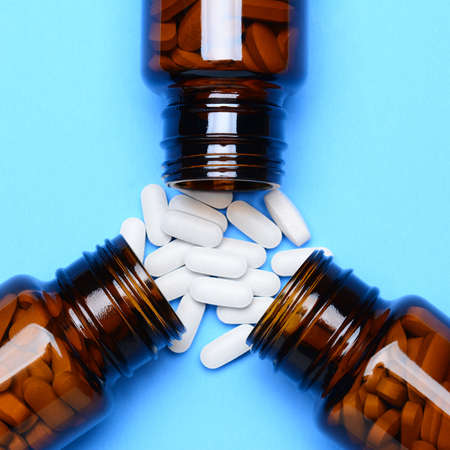 A closeup of three prescription medicine bottles laying on their sides with pills spilling onto a blue surface  Overhead shot with the bottles as the main focus  photo