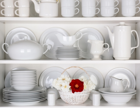 Closeup of white plates and dinnerware in a cupboard  A basket of white and red roses is centered on the bottom shelf  Items include, plates, coffee cups, saucers, soup tureen, tea pot, and gray boats  photo