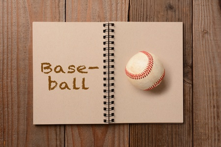 A worn baseball on the blank page of a notebook  The opposite page has the word Baseball spelled out  Horizontal format on a rustic wooden table