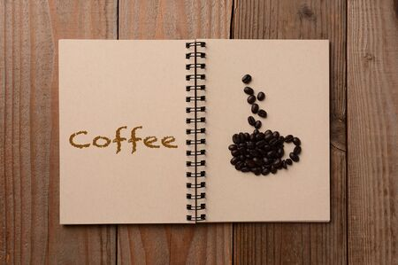 A group of coffee beans shaped into a coffee cup on the blank page of a notebook  The opposite page has the word Coffee spelled out  Horizontal format on a rustic wooden table