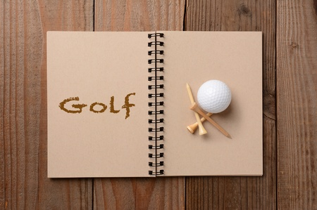 A golf ball and tees on the blank page of a notebook  The opposite page has the word Golf spelled out  Horizontal format on a rustic wooden table