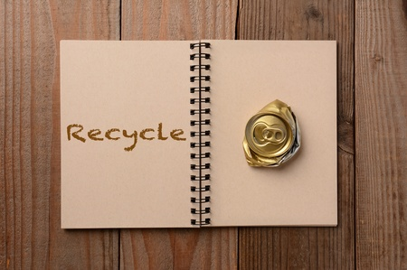 A crushed soda can on the blank page of a notebook  The opposite page has the word Recycle spelled out  Horizontal format on a rustic wooden table  photo