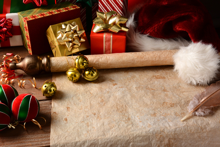 A Christmas Still Life with an old parchment scroll, presents, ornaments and a Santa Hat  Closeup in horizontal format with strong side light   This could be Santa photo