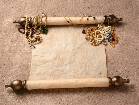 Piraten buit Een oude rol tot op het strand zand met juwelen verspreid over het bovenste uiteinde De scroll is leeg klaar voor uw schatkaart of kopie Stockfoto