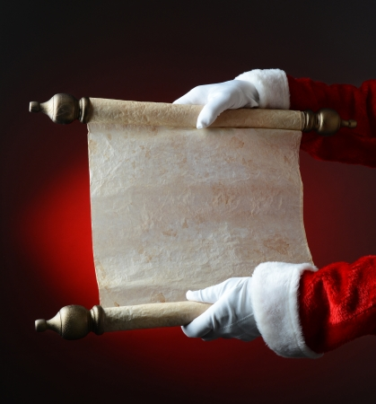 Santa holding naughty and nice scroll over a light to dark red The scroll is blank, ready for your copy  Only Santa Claus
