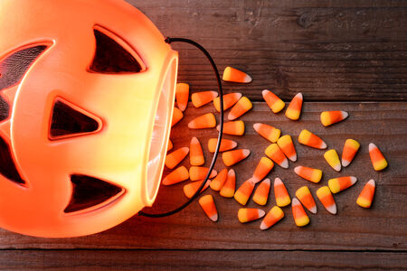 trick or treat: Plastic pumpkin and candy corn spill on a rustic wood Perfect for Halloween themed projects