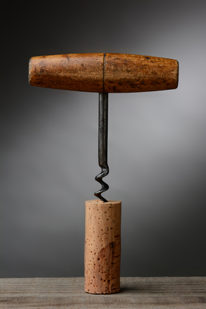 wine cork: Closeup of an antique corkscrew stuck in a cork over a light to dark gray