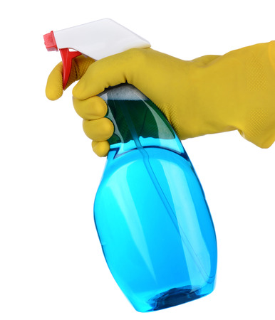 finger on trigger: Closeup of a plastic spray bottle of cleaner being held by a hand wearing a yellow latex glove  Vertical format isolated on white  The cleanser   chemical is blue and the persons finger is on the trigger nozzle  Stock Photo