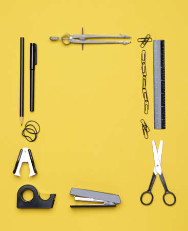 office stapler: Office and back to school supplies on a yellow background  Looking down on the all black and chrome tools from an overhead angle  The items are arranged in a rectangle forming a frame