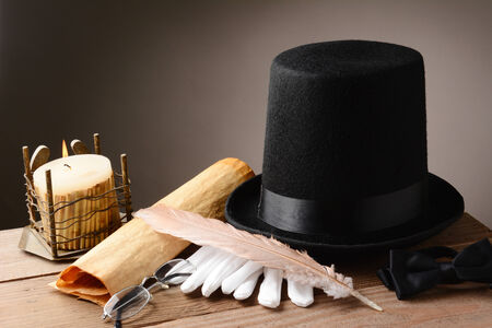 stovepipe hat: Still life with and old hat gloves quill candle and parchment on rustic wooden table  Horizontal format with warm colors and a light to dark  Stock Photo