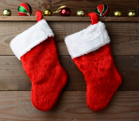 Two Christmas stockings hung on a rustic wooden wall with sliegh bells and ornaments  Stockfoto