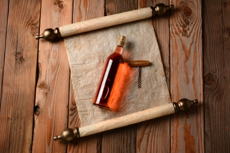 A bottle of blush wine and corkscrew laying on a scroll of parchment paper on a rustic wooden floor  photo