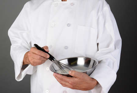 chrome man: Closeup of a Chef holding a stainless steel mixing bowl and a whisk  Horizontal format on a light to dark gray background, Man is unrecognizable  Model Released