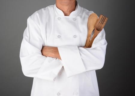 男は認識できない横向き木製の道具を保持している彼の腕を持つシェフのクローズ アップが折り畳まれて発売暗い灰色の背景に光 写真素材