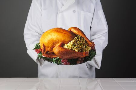 Closeup of a chef holding a platter with a Thanksgiving Turkey with all the trimmings  Horizontal format over a light to dark background  Man is unrecognizable  Model Released  photo