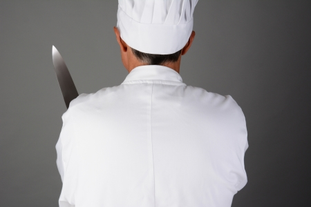 Closeup of a chef holding a knife  Man is seen from behind and is unrecognizable  Horizontal format on a light to dark gray background  Model Released  photo