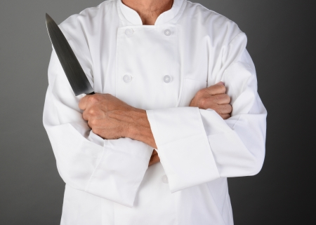 and the horizontal man: Closeup of a chef with his arms folded holding a knife  Man is unrecognizable  Horizontal format on a light to dark gray background  Model Released
