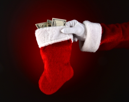 Closeup of Santa Claus holding a stocking full of cash  Only Santa
