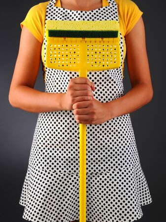 homemaker: Closeup of a homemaker in an apron holding a sponge mop in front of her torso  Vertical format over a light to dark background  Woman is unrecognizable