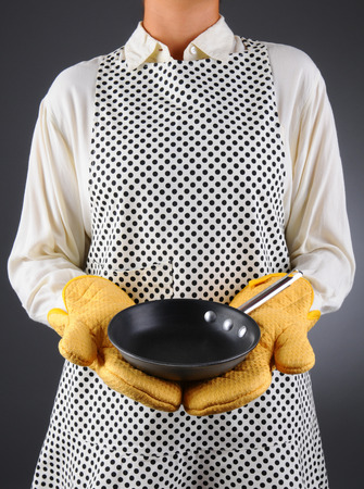 Closeup of a homemaker in an apron and oven mitts holding a pan  Vertical format over a light to dark background  Woman is unrecognizable  The pan is empty - ready for you to add food or copy