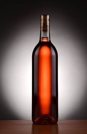 A blush wine bottle backlit with a light to dark spot background  Vertical format