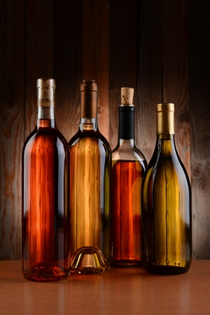 Four wine bottles against a wood background  The bottles have no label and the texture of the background shows through  Vertical format