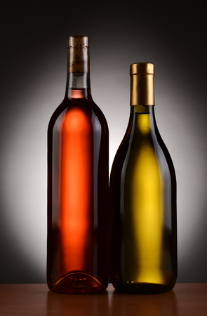 Closeup of two wine bottles backlit with a light to dark gray background  Blush and Chardonnay bottles are shown in full length  Vertical Format Stock Photo - 23121768