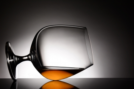Closeup of a brandy snifter laying on it side  Horizontal format with a light to dark gray spot background  The glass is on a shiny black reflective surface
