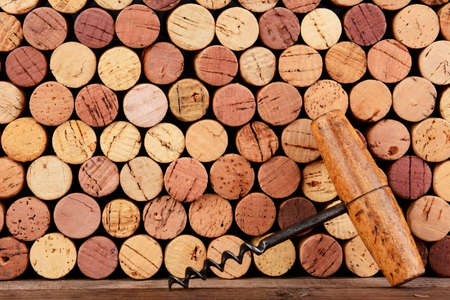cork screw: Closeup of an antique cork screw leaning against a wall of use corks  Horizontal format filling the frame
