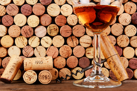 white zinfandel: Closeup of a wineglass in front of a wall of used corks  An antique cork screw and dated corks are adjacent to the glass  Horizontal format filling the frame