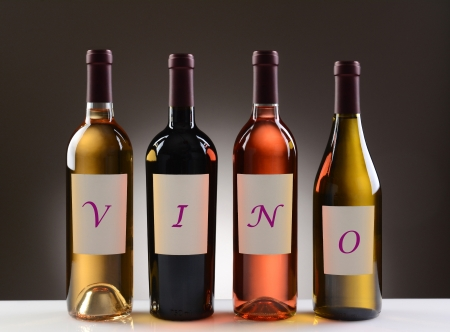 Four Wine Bottles with their labels spelling out the word VINO, on a light to dark gray background  Four different wines including  Cabernet Sauvignon, Chardonnay, Sauvignon Blanc, and White Zinfandel  photo