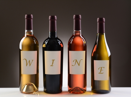white zinfandel: Four Wine Bottles with their labels spelling out the word WINE, on a light to dark gray background  Four different wines including  Cabernet Sauvignon, Chardonnay, Sauvignon Blanc, and White Zinfandel  Stock Photo