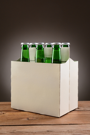 6 pack beer: Closeup of a six pack of green beer bottles on a rustic wooden table. Vertical format with a light to dark gray spot background. Stock Photo
