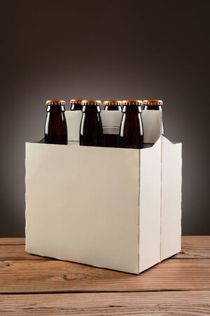 Closeup of a six pack of brown beer bottles on a rustic wooden table. Vertical format with a light to dark gray spot background. Standard-Bild
