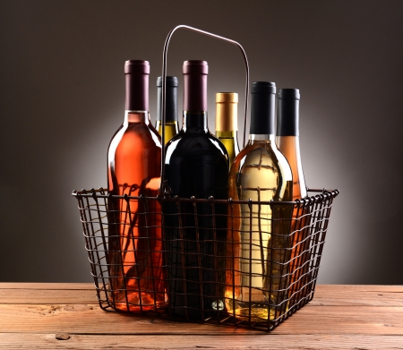 A wire shopping basket filled with assorted wine bottles. The basket is sitting on a rustic wooden table with a light to dark gray spot background. Stock Photo - 23301766
