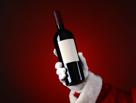 Closeup of Santa Claus holding a bottle of wine in his hand. Hand and arm only over a light to dark red spot .