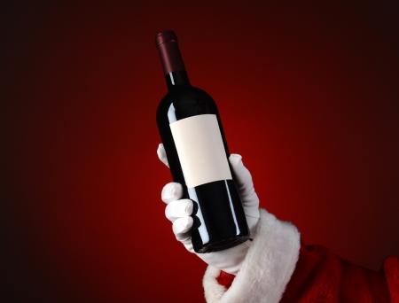 Gros plan du Père Noël tenant une bouteille de vin à la main. Main et le bras que sur une lumière de tache rouge sombre. Banque d'images - 23322853