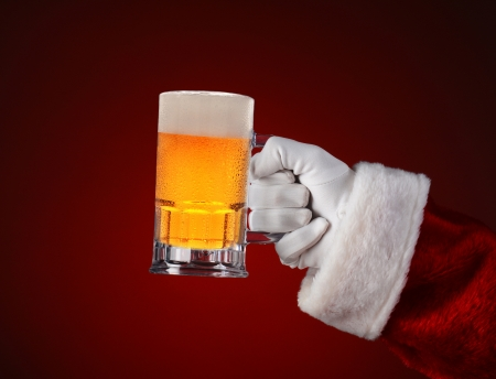 ale: Closeup of Santa Claus holding a mug of beer. Horizontal format on a light to dark red spot .