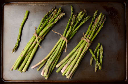 Bunches of Asparagus tied with twine on a metal cooking sheet  Horizontal format filling the frame  photo