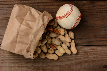 ballgame: A bag of peanuts and a baseball on an old wooden bench at the ballpark  The paper bag is on its side with the nuts spilling out   Horizontal format with copy space