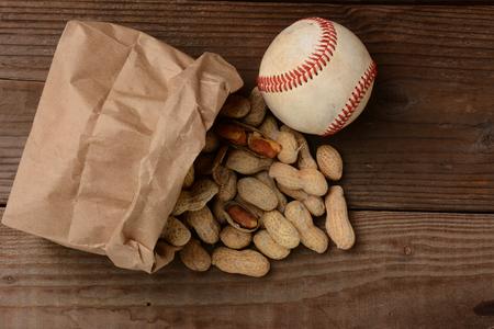 ballpark: Una bolsa de cacahuetes y una pelota de b�isbol en un viejo banco de madera en el estadio La bolsa de papel es en su lado con las nueces derrame fuera de formato horizontal, con copia espacio