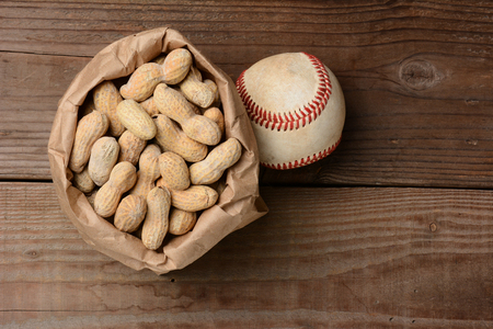 ballpark: A bag of peanuts and a baseball on an old wooden bench at the ballpark  Horizontal format with copy space  Stock Photo