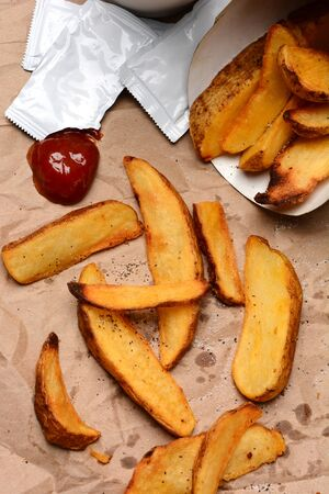 fench: French Fries spilled onto a brown bag  Ketchup dollop and packets  with salt and pepper  Vertical format filling the frame