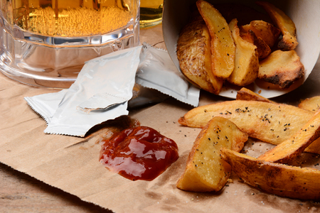 French Fries spilled onto a brown bag  Ketchup dollop and packets  with salt and pepper and mug of beer  Horizontal format filling the frame