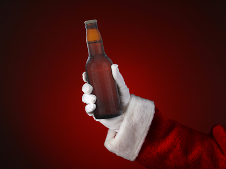 Closeup of Santa Claus holding a bottle of beer  Only hand and arm are visible  Horizontal format on a light to dark red spot background  Stockfoto