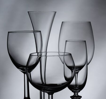 stemware: Five wine and champagne glasses against a gray mottled background. Square Format.