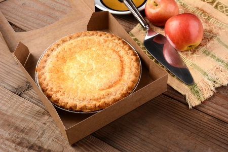 serving utensil: Closeup of a fresh apple pie in a bakery box on a rustic wood table. A plate, serving utensil and fresh Fuji apples are in the background. Horizontal format. Stock Photo