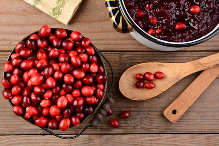 Overhead of a bucket of cranberries and a pot full of whole cranberry sauce on a rustic wooden table. Cranberry sauce is a traditional Thanksgiving side dish. Horizontal format. Stock Photo